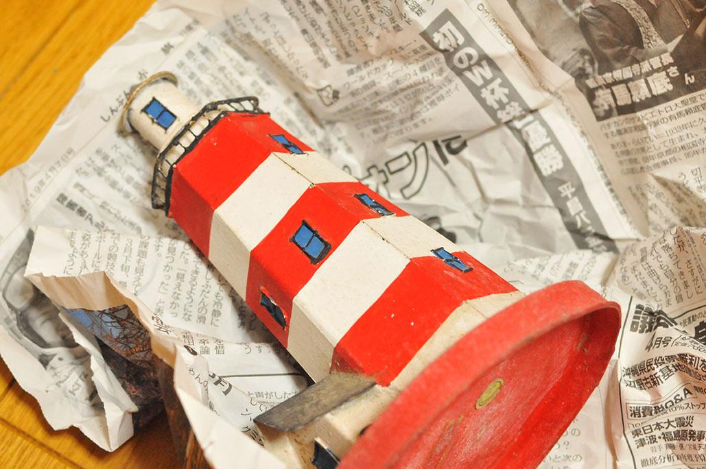 古道具プレゼントの包みを開けると可愛い灯台のオブジェが!