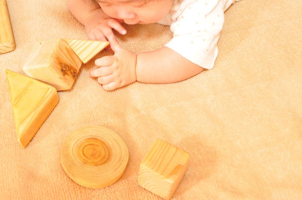 手作りの積み木を見つけて遊ぶ赤ちゃん