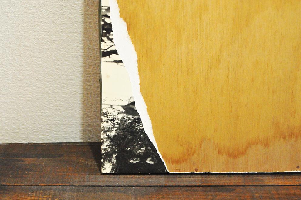 モノクロ写真が貼ってあったであろう木製ボードの表面