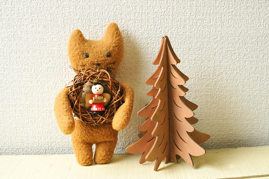 小さなクリスマスリースを抱っこしてもみの木のそばでポーズをとる手作りぬいぐるみ