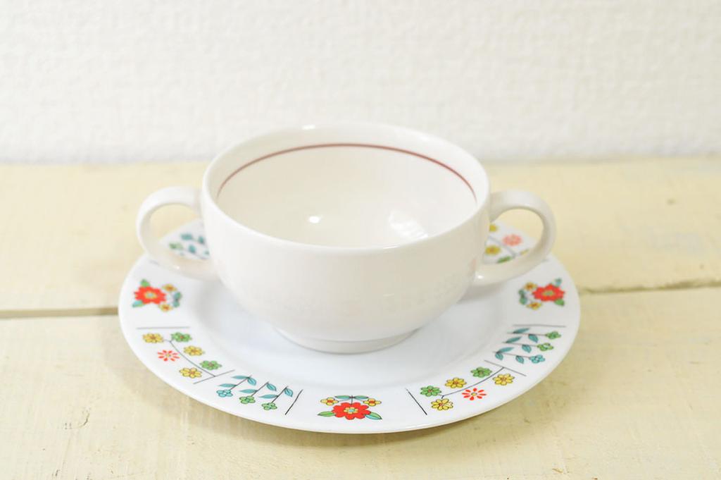 シンプルなラインが入ったオフホワイトのカップをレトロな模様のお皿にのせて