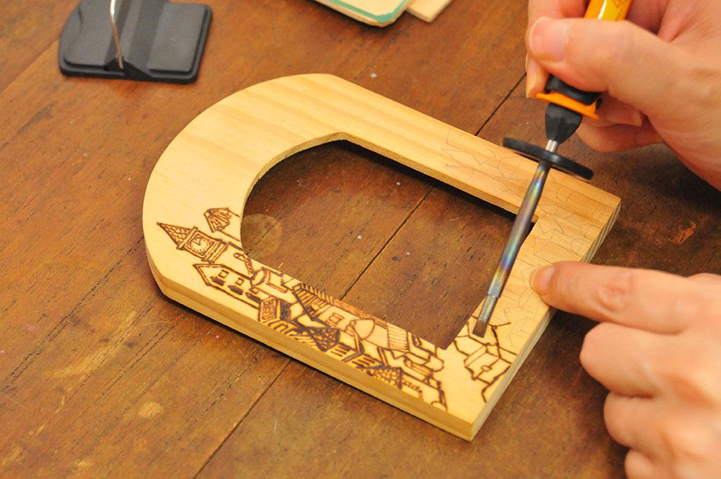 電気ペン「ヒーティングツール」で木製フレームに絵を描いていく
