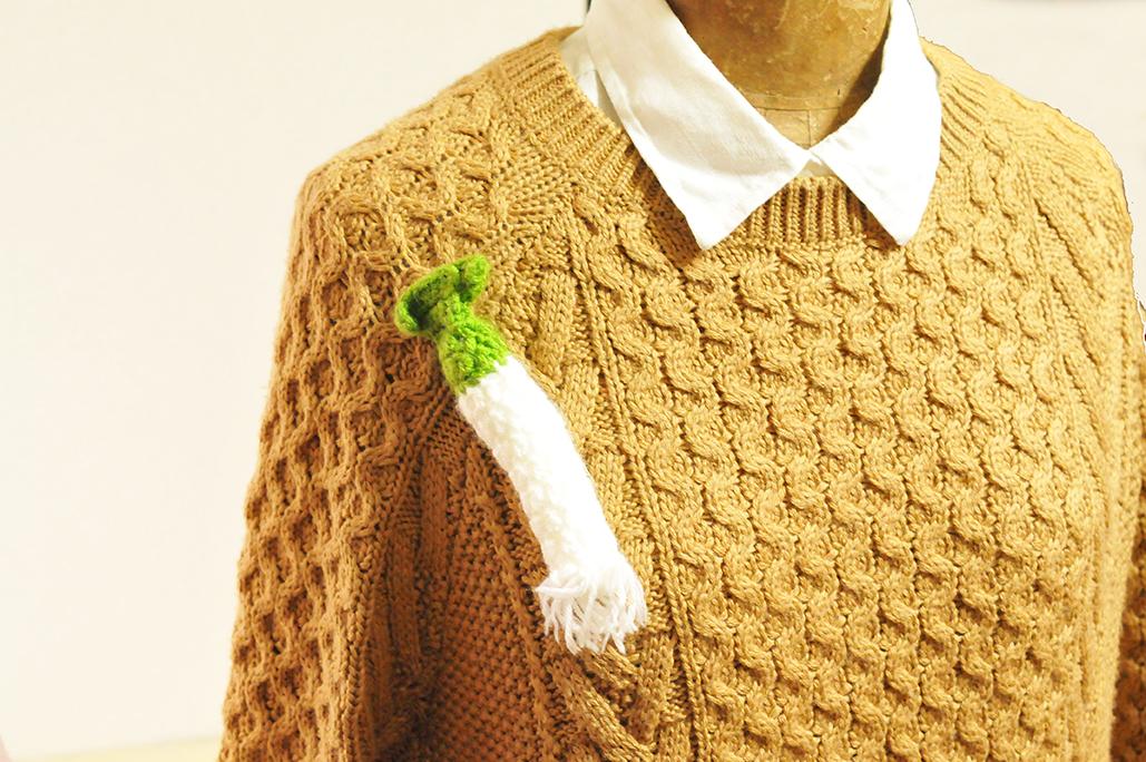 セーターにつけたウェールズ国花のネギの編みブローチ